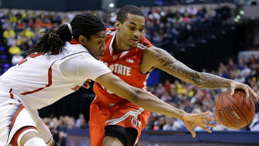 Nebraska forward David Rivers, left, tries to steal a ball from Ohio State forward LaQuinton Ross in the first half of an NCAA college basketball game in the quarterfinals of the Big Ten Conference tournament Friday, March 14, 2014, in Indianapolis. (AP Photo/Michael Conroy)