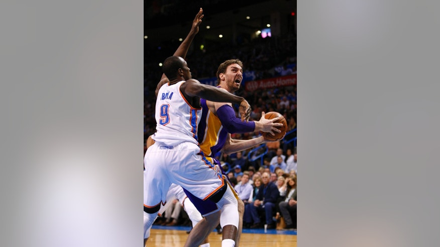 Oklahoma City Thunder forward Serge Ibaka (9) defends as Los Angeles Lakers center Pau Gasol (16) goes to the basket during the first quarter of an NBA basketball game in Oklahoma City, Thursday, March 13, 2014. (AP Photo/Alonzo Adams)