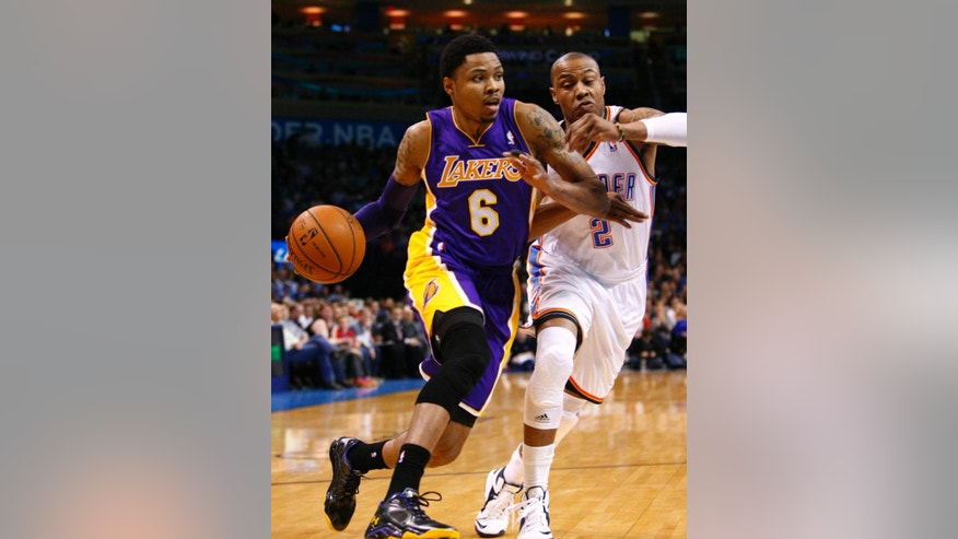 Los Angeles Lakers guard Kent Bazemore (6) drives to the basket around Oklahoma City Thunder forward Caron Butler (2) during the first quarter of an NBA basketball game in Oklahoma City, Thursday, March 13, 2014. (AP Photo/Alonzo Adams)
