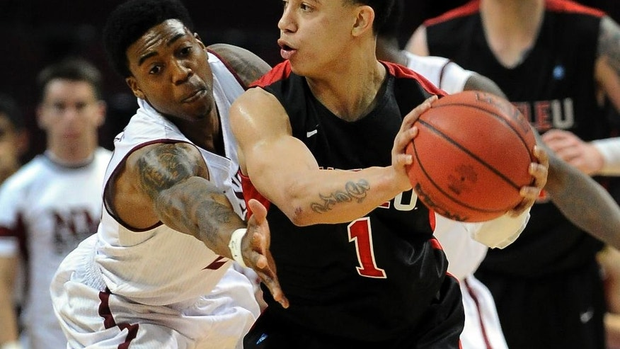 Seattle's Isiah Umipig (1) keeps the ball away from New Mexico State's Daniel Mullings during the first half of an NCAA college basketball game in the first round of the West Athletic Conference men's tournament Thursday, March 13, 2014, in Las Vegas. (AP Photo/David Becker)