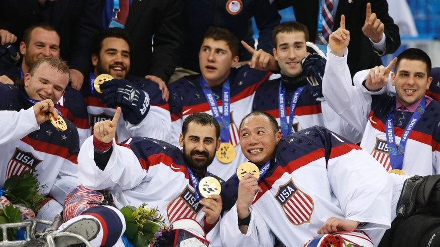 March 15, 2014: United States players pose for a team photo after winning the gold medal after their ice sledge hockey match against Russia at the 2014 Winter Paralympics in Sochi, Russia.