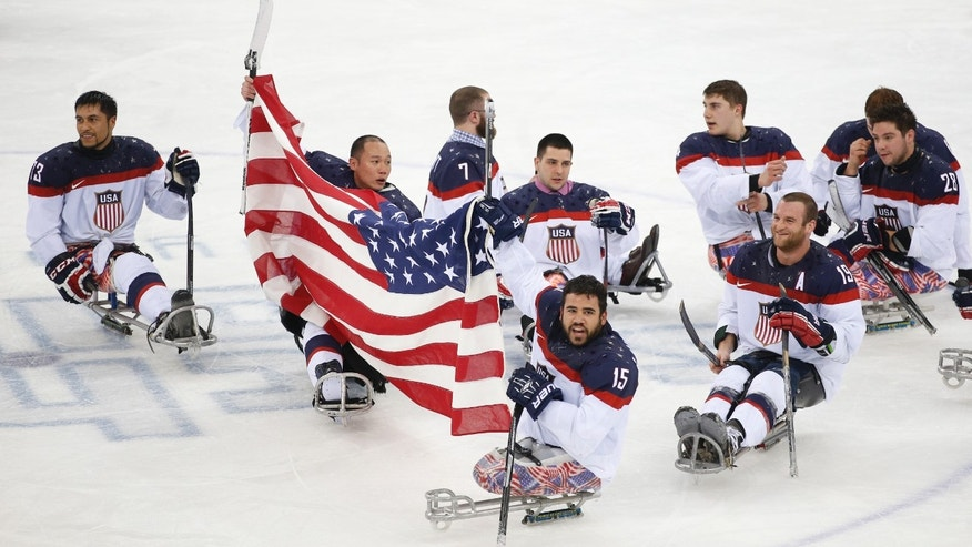 United States players celebrate as they win the gold medal after their ice sledge hockey match against Russia at the 2014 Winter Paralympics in Sochi, Russia, Saturday, March 15, 2014. United States won 1-0. (AP Photo/Pavel Golovkin)