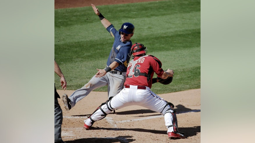 Milwaukee Brewers' Scooter Gennett, is tagged out by Arizona Diamondbacks catcher Miguel Montero while trying to score on a hit by Jonathan Lucroy during the fifth inning of a spring exhibition baseball game in Scottsdale, Ariz., Sunday, March 16, 2014. (AP Photo/Chris Carlson)