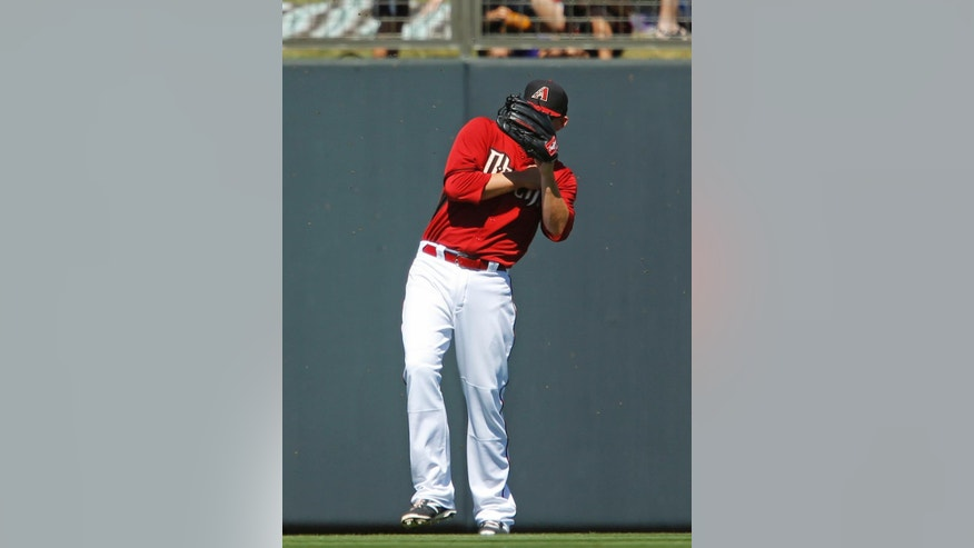 Arizona Diamondbacks' Mark Trumbo does his best to avoid a swarm of bees as he plays left field against the Milwaukee Brewers during their Cactus League game, Sunday, March 16, 2014 at Salt River Fields in Scottsdale, Ariz. (AP Photo/The Arizona Republic, David Kadlubowski)