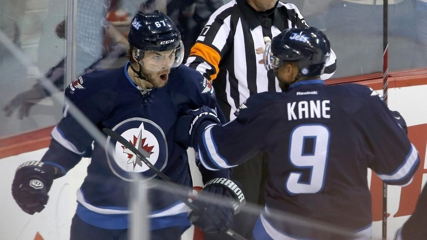 Winnipeg Jets' Michael Frolik (67) celebrates with Evander Kane (9) after scoring against the Dallas Stars' during first period NHL action at the MTS Centre in Winnipeg, Manitoba,  Sunday, March 16, 2014. (AP Photo/The Canadian Press, Trevor Hagan)