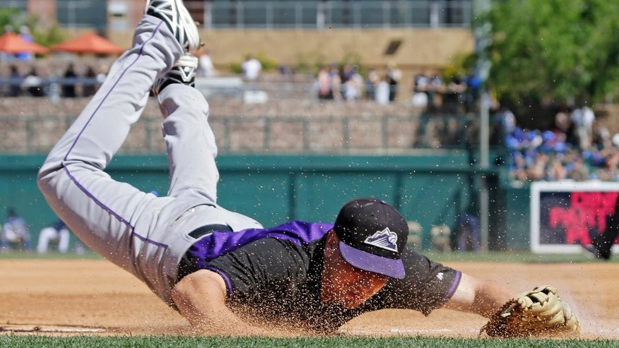 Colorado Rockies catcher Matt McBride dives but cannot get to a ground ball down the line for a double hit by Los Angeles Dodgers' Carl Crawford in the fourth inning of a spring exhibition baseball game on Sunday, March 16, 2014, in Glendale, Ariz. (AP Photo/Mark Duncan)