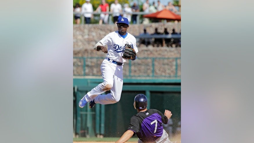 Los Angeles Dodgers shortstop Dee Gordon, top, jumps over Colorado Rockies' Matt McBride (7) after a force at second in the sixth inning of a spring exhibition baseball game on Sunday, March 16, 2014, in Glendale, Ariz. Gordon's throw pulled first baseman Adrian Gonzalez off the bag and Rockies' Charlie Culberson was safe. (AP Photo/Mark Duncan)