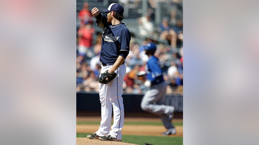 San Diego Padres starting pitcher Ian Kennedy wipes his face after giving up a solo home run to Kansas City Royals' Carlos Peguero during the third inning of a spring exhibition baseball game Sunday, March 16, 2014, in Peoria, Ariz. (AP Photo/Darron Cummings)