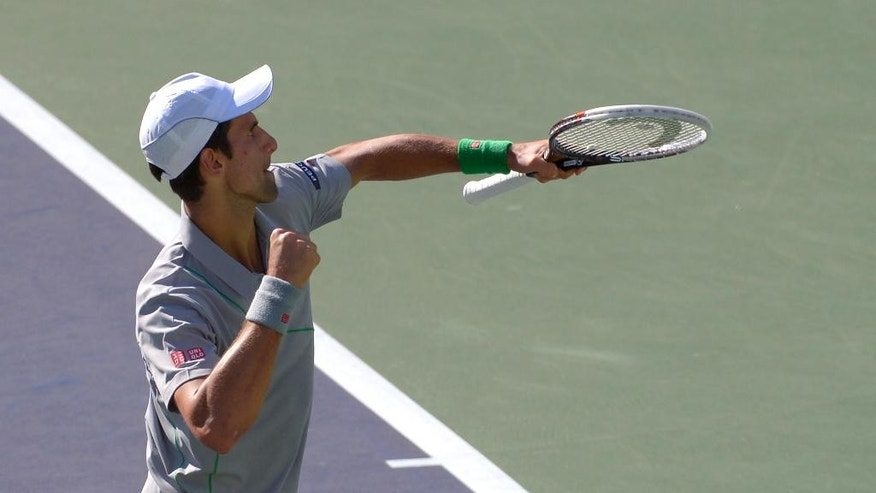 Novak Djokovic, of Serbia, pumps his fist after hitting a shot to Roger Federer, of Switzerland, in the final match of the BNP Paribas Open tennis tournament, Sunday, March 16, 2014, in Indian Wells, Calif. (AP Photo/Mark J. Terrill)