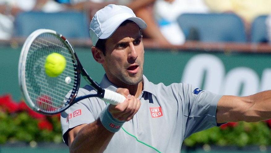 Novak Djokovic, of Serbia, hits a shot from Roger Federer, of Switzerland, in the final match of the BNP Paribas Open tennis tournament, Sunday, March 16, 2014, in Indian Wells, Calif. (AP Photo/Mark J. Terrill)