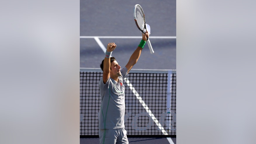 Novak Djokovic, of Serbia, celebrates on the court after he beat Roger Federer, of Switzerland, 3-6, 6-3, 7-6 to win the final match of the BNP Paribas Open tennis tournament, Sunday, March 16, 2014, in Indian Wells, Calif. (AP Photo/Mark J. Terrill)