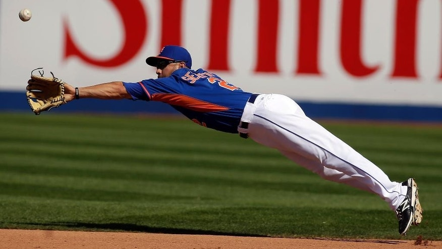New York Mets second baseman Anthony Seratelli dives for the ball during a spring exhibition baseball game against the Chicago Cubs, Sunday, March 16, 2014, in Las Vegas. (AP Photo/Isaac Brekken)