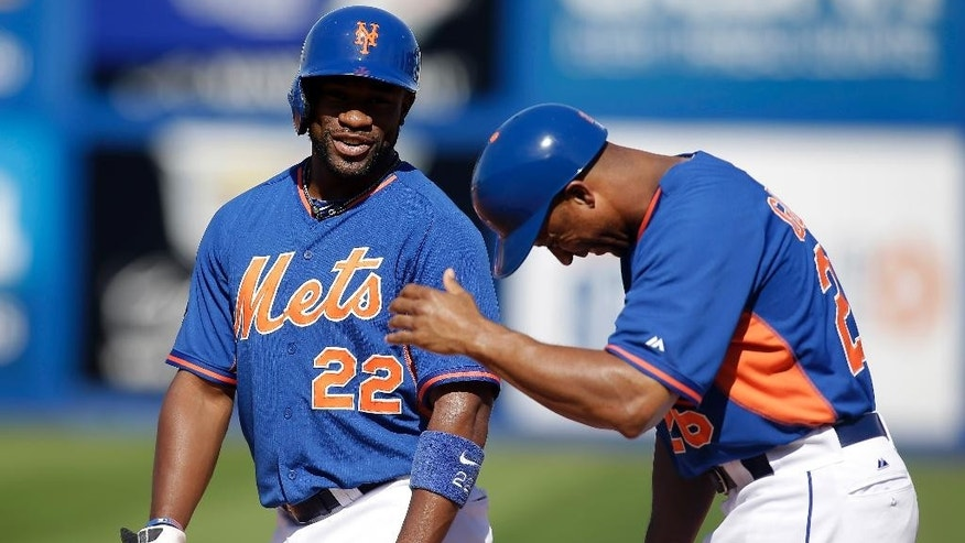 New York Mets Eric Young Jr., left, and first base coach Tom Goodwin laugh during a spring exhibition baseball game against the Chicago Cubs, Sunday, March 16, 2014, in Las Vegas. (AP Photo/Isaac Brekken)
