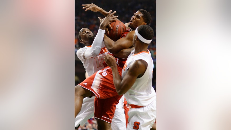 North Carolina State forward Lennard Freeman (10) fights for the ball with Syracuse center Baye-Moussa Keita, left, and forward C.J. Fair (5) during an NCAA college basketball game in the quarterfinal round of the Atlantic Coast Conference tournament in Greensboro, N.C., Friday, March 14, 2014. (AP Photo/Burlington Times-News, Scott Muthersbaugh)