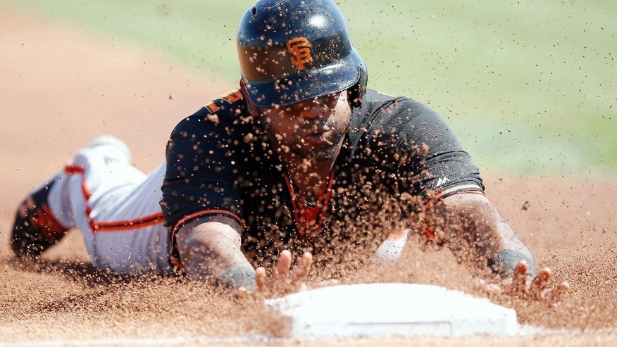 San Francisco Giants' Pablo Sandoval slides safely to third base, advancing on a single by teammate Mark Minicozzi, in the first inning of a spring training baseball game against the Los Angeles Angels, Monday, March 17, 2014, in Tempe, Ariz. (AP Photo/Ross D. Franklin)
