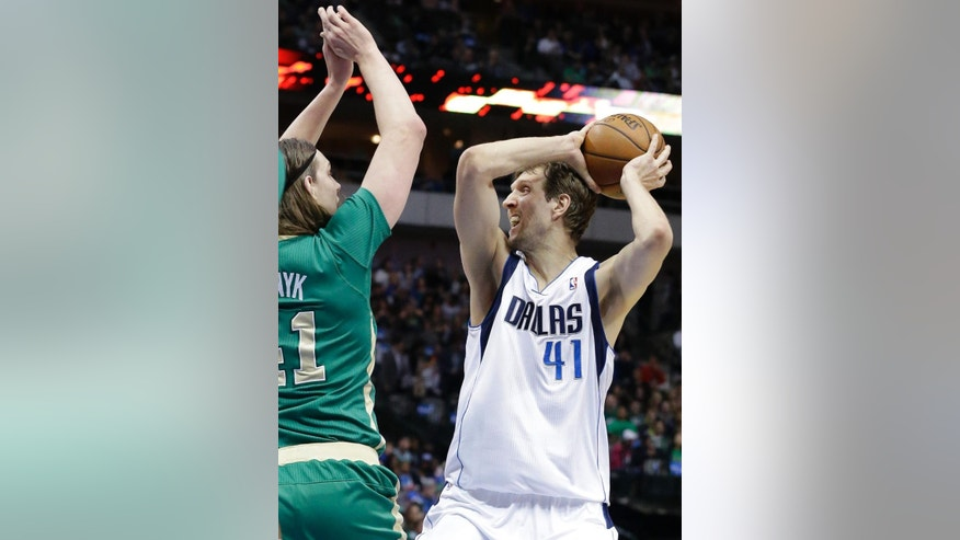 Dallas Mavericks forward Dirk Nowitzki (41) of Germany looks to pass against Boston Celtics center Kelly Olynyk (41) during the first half an NBA basketball game Monday, March 17, 2014, in Dallas. (AP Photo/LM Otero)