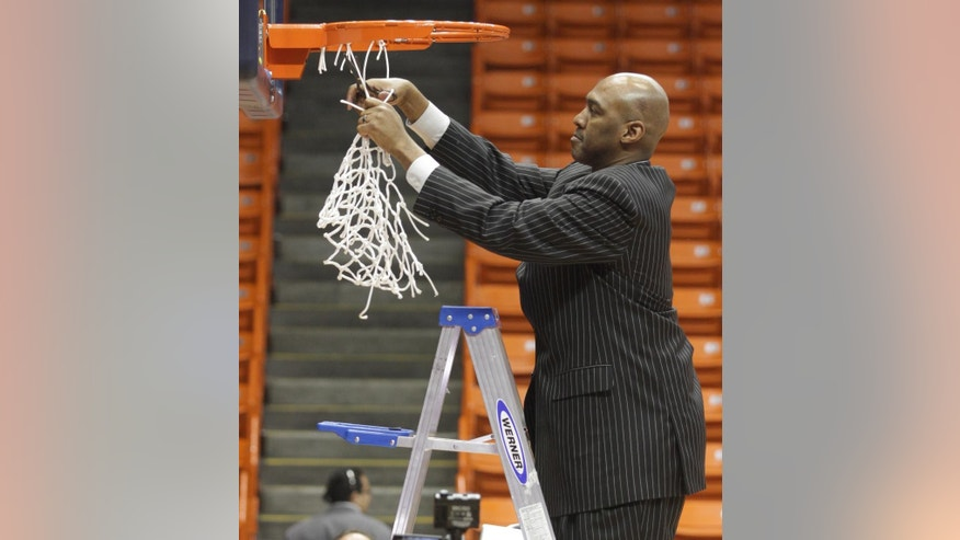 Tulsa head basketball coach Danny Manning makes the final cut on the net after his team's Conference USA Tournament championship game victory Saturday  March 15, 2014 in El Paso, Texas. (AP Photo/Victor Calzada)