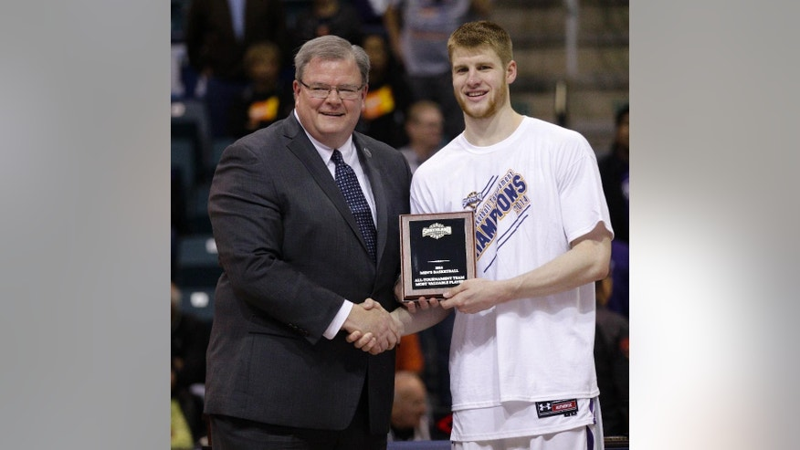 Southland Conference commissioner  Tom Burnett, left, presents Stephen F. Austin's Thomas Walkup with the  All-Tournament Team Most Valuable Player award during the second half of an NCAA college basketball game in the championship of the Southland Conference tournament Saturday, March 15, 2014, in Katy, Texas. Stephen F. Austin won 68-49. (AP Photo/Bob Levey)