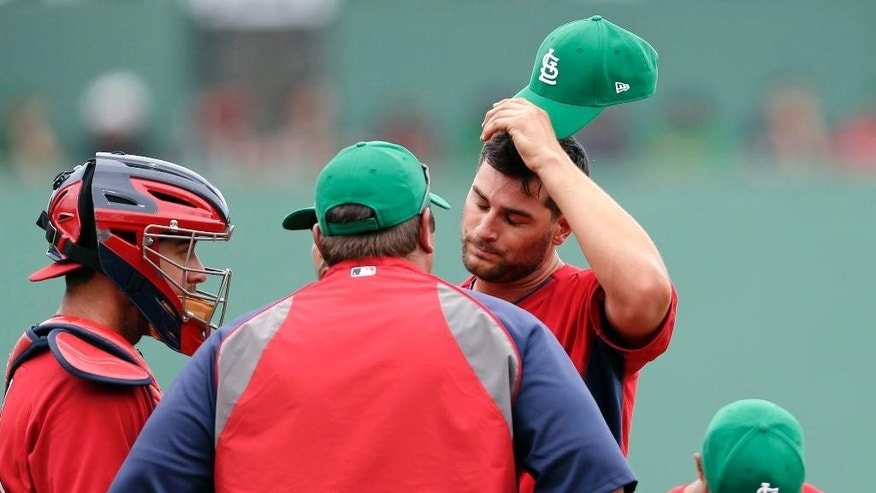 St. Louis Cardinals pitcher Tyler Lyons, right, talks on the mound with pitching coach Derek Lilliquist and catcher Tony Cruz, left, after giving up a three-run homer to Boston Red Sox Mike Napoli in the fifth inning of an exhibition baseball game in Fort Myers, Fla., Monday, March 17, 2014. (AP Photo/Gerald Herbert)