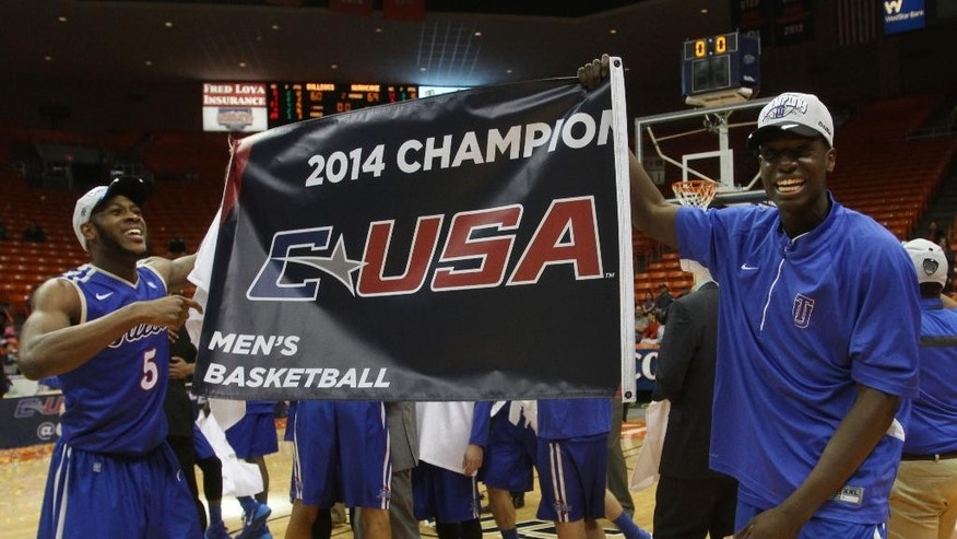 Tulsa players hold up a championship sign in celebratioin of their Conference USA Tournament championship game victory  over Louisiana Tech Saturday  March 15, 2014 in El Paso, Texas. (AP Photo/Victor Calzada)