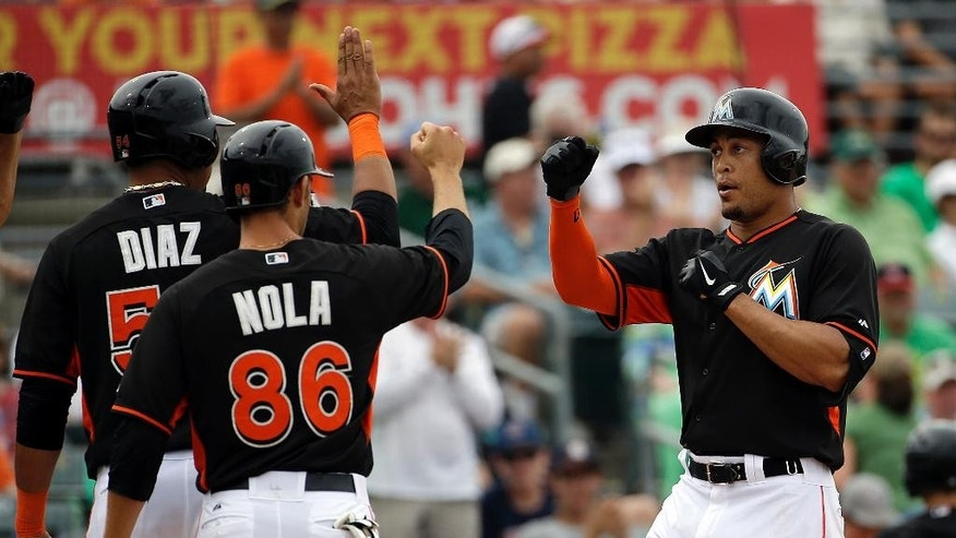 Miami Marlins' Giancarlo Stanton, right, is high-fived by teammates Juan Diaz, left, and Austin Nola after the trio scored off Stanton's home run in the sixth inning of an exhibition spring training baseball game against the New York Mets, Monday, March 17, 2014, in Jupiter, Fla. (AP Photo/David Goldman)