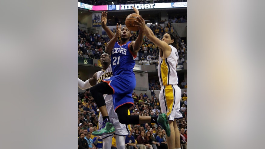 Philadelphia 76ers forward Thaddeus Young, center, drives between Indiana Pacers defenders Ian Mahinmi, left, and Luis Scola, of Argentina, during the first half of an NBA basketball game in Indianapolis, Monday, March 17, 2014. (AP Photo/AJ Mast)