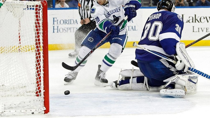 Vancouver Canucks right wing Jannik Hansen, center, shoots and scores against Tampa Bay Lightning goalie Ben Bishop (30) during the third period of an NHL hockey game Monday, March 17, 2014, in Tampa, Fla. (AP Photo/Brian Blanco)
