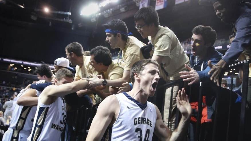 George Washington forward John Kopriva (34) celebrates with fans after an NCAA college basketball game against Massachusetts in the quarterfinals of the Atlantic 10 Conference men's tournament in New York, Friday, March 14, 2014. George Washington won 85-77. (AP Photo/John Minchillo)