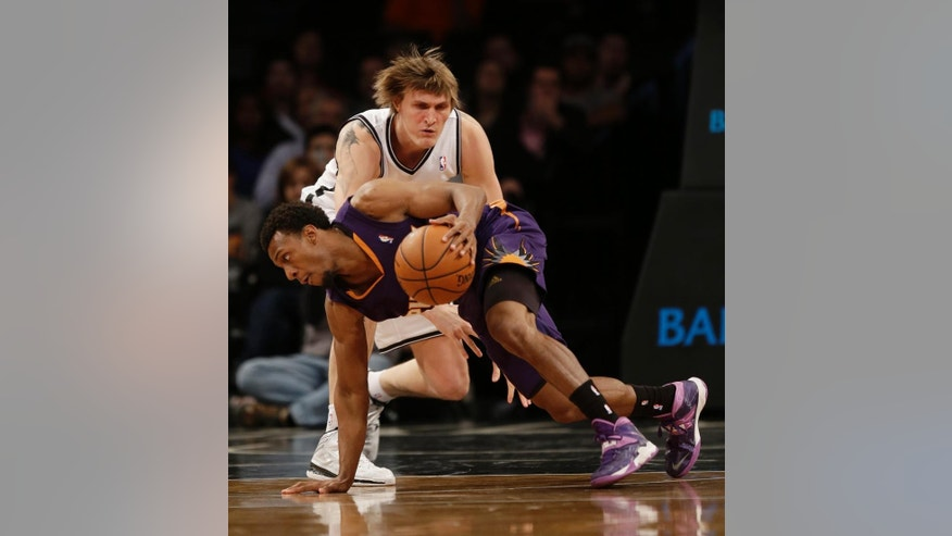 Phoenix Suns' Ish Smith, bottom, gets control of the ball while Brooklyn Nets's Andrei Kirilenko defends during the first half of the NBA basketball game at the Barclays Center Monday, March 17, 2014 in New York. (AP Photo/Seth Wenig)