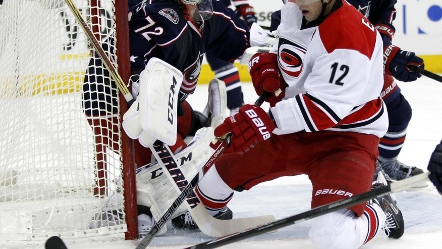 Carolina Hurricanes' Eric Staal, right, tries to settle the puck in front of Columbus Blue Jackets goalie Sergi Bobrovsky, of Russia,  in the first period of an NHL hockey game in Columbus, Ohio, Tuesday, March 18, 2014. (AP Photo/Paul Vernon)