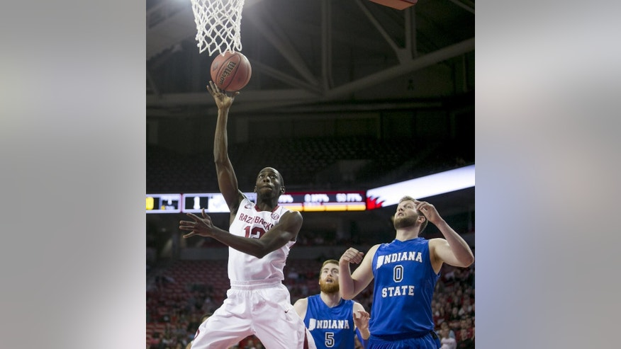 Arkansas guard Fred Gulley III (12) shoots a layup after weaving through Indiana State defenders Justin Gant (5) and Jake Kitchell (0) during the first half of an opening round National Invitational Tournament NCAA college basketball game in Fayetteville, Ark., Tuesday, March 18, 2014. (AP Photo/Gareth Patterson)