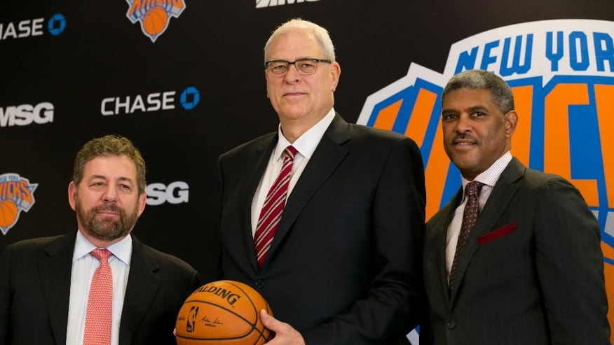 New York Knicks new team president Phil Jackson, center, poses for photos with team owner James Dolan, left, and general manager Steve Mills, during a news conference where he was introduced, at New York's Madison Square Garden, Tuesday, March 18, 2014. (AP Photo/Richard Drew)