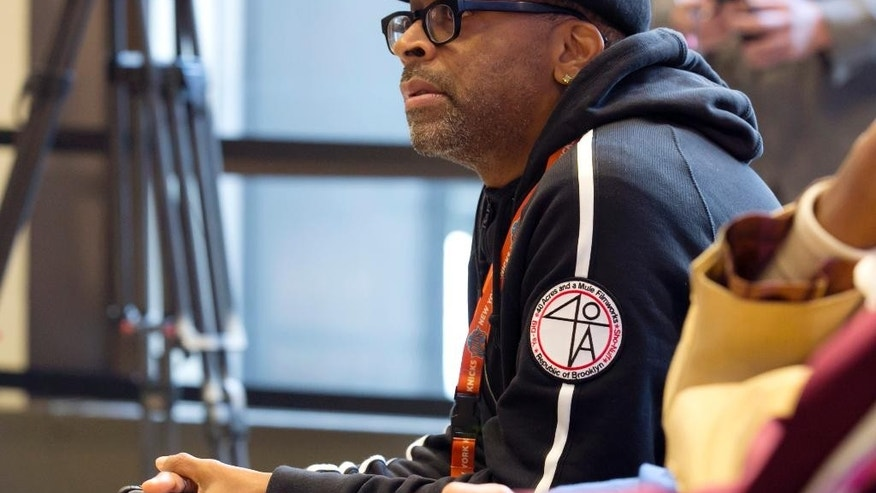 Filmmaker Spike Lee listens as New York Knicks new team president Phil Jackson addresses a news conference where he was introduced, at New York's Madison Square Garden, Tuesday, March 18, 2014. (AP Photo/Richard Drew)