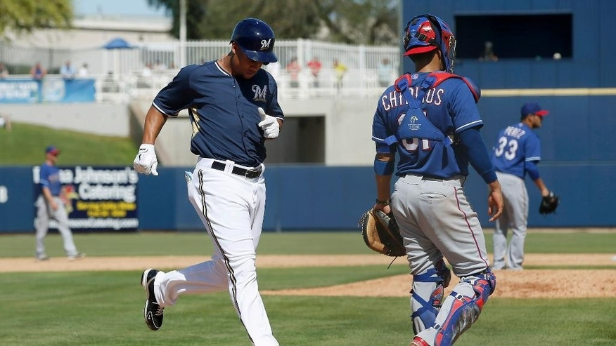 Milwaukee Brewers' Carlos Gomez, left, scores a run as Texas Rangers catcher Robinson Chirinos and pitcher Martin Perez (33) look elsewhere during the fourth inning of a spring training baseball game, Tuesday, March 18, 2014, in Phoenix. (AP Photo/Ross D. Franklin)