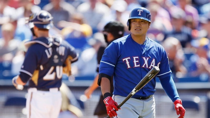 Texas Rangers' Shin-Soo Choo, right, of South Korea, walks back to the dugout after striking out as Milwaukee Brewers' Jonathan Lucroy (20) looks back into his dugout during the first inning of a spring training baseball game, Tuesday, March 18, 2014, in Phoenix. (AP Photo/Ross D. Franklin)