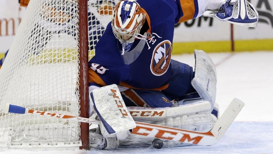 New York Islanders goalie Anders Nilsson makes a save during the first period of the NHL hockey game against the Minnesota Wild, Tuesday, March 18, 2014, in Uniondale, New York. (AP Photo/Seth Wenig)