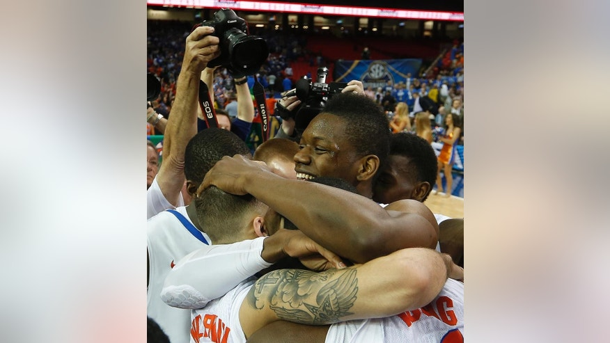Florida forward Will Yeguete (15) embraces team mates after the second half of an NCAA college basketball game against Kentucky in the Championship round of the Southeastern Conference men's tournament, Sunday, March 16, 2014, in Atlanta. Florida won 61-60. (AP Photo/John Bazemore)