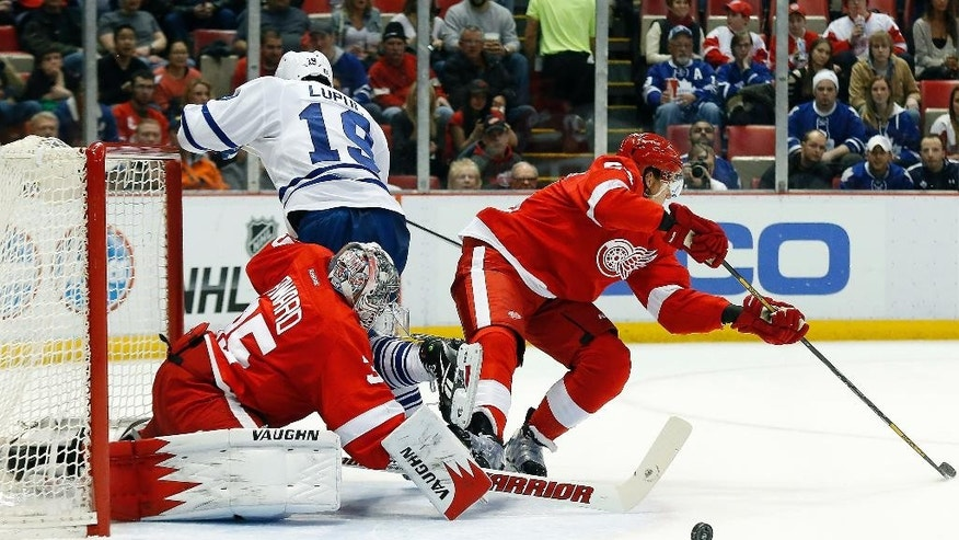 Detroit Red Wings goalie Jimmy Howard (35) stops a Toronto Maple Leafs right wing Joffrey Lupul (19) shot as defenseman Danny DeKeyser defends in the first period of an NHL hockey game in Detroit, Tuesday, March 18, 2014. (AP Photo/Paul Sancya)