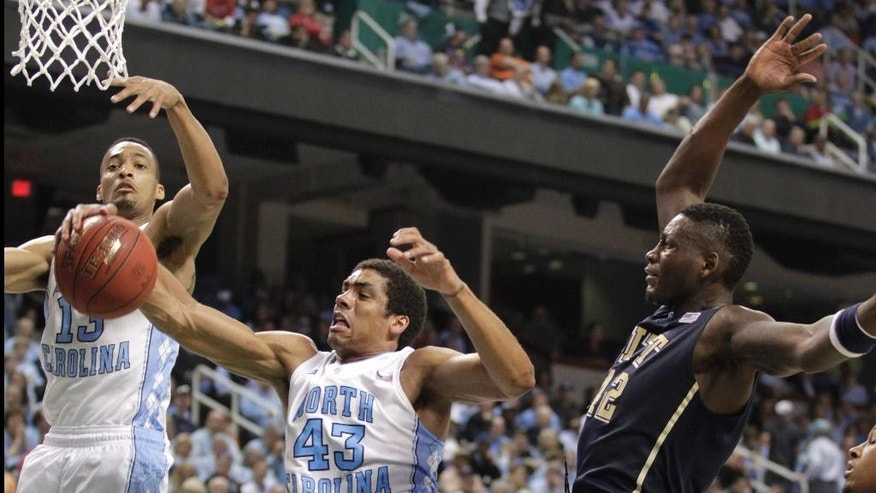 Pittsburgh's Talib Zanna, right, battles for a rebound with North Carolina's James Michael McAdoo, center, and J.P. Tokoto, left, during the second half of an NCAA college basketball game in the quarterfinal round of the Atlantic Coast Conference tournament in Greensboro, N.C., Friday, March 14, 2014. (AP Photo/Bob Leverone)