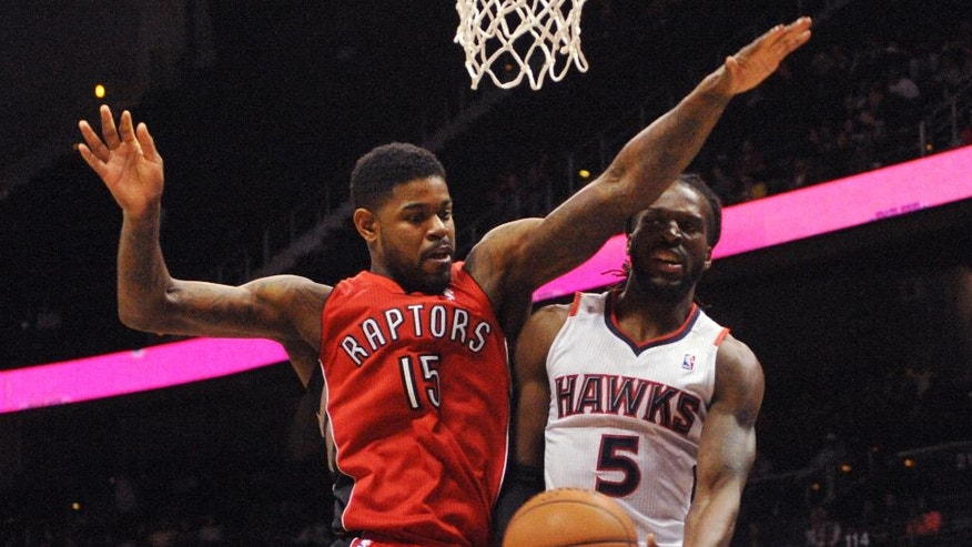 Atlanta Hawks forward DeMarre Carroll (5) passes around Toronto Raptors' Amir Johnson (15) in the first half of their NBA basketball game Tuesday, March 18, 2014, in Atlanta. (AP Photo/David Tulis)