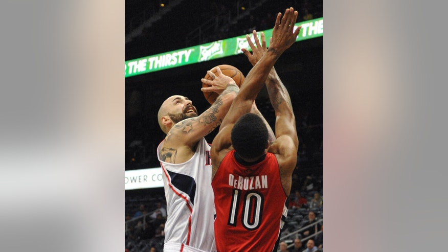 Atlanta Hawks' Pero Antic (6) shoots over Toronto Raptors' DeMar DeRozan (10) in the first half of their NBA basketball game Tuesday, March 18, 2014, in Atlanta. (AP Photo/David Tulis)