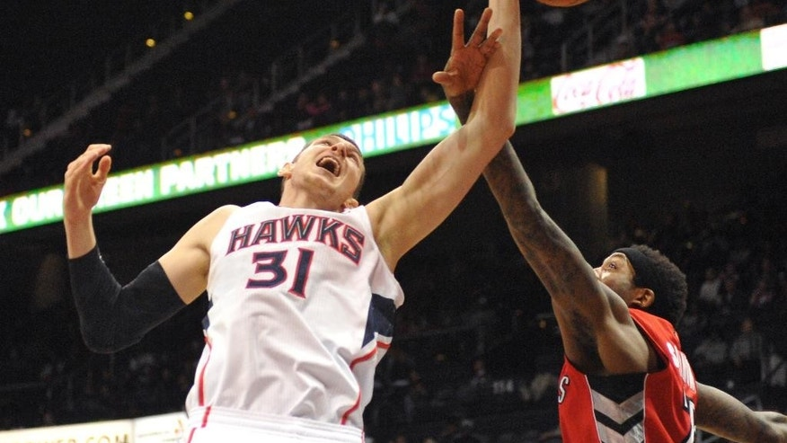 Toronto Raptors' John Salmons, right, makes contact with Atlanta Hawks' Mike Muscala (31) in the first half of their NBA basketball game Tuesday, March 18, 2014, in Atlanta. (AP Photo/David Tulis)