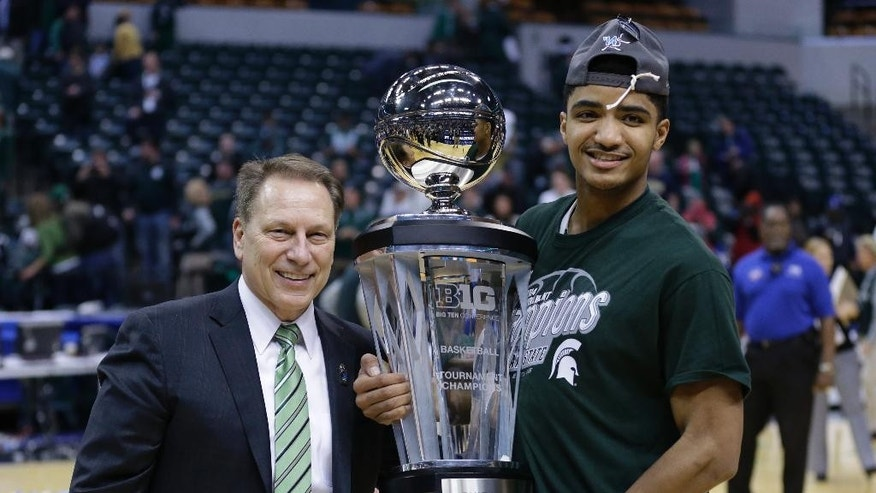 Michigan State head coach Tom Izzo, left, and guard Gary Harris pose with the championship trophy after they defeated Michigan 69-55 in an NCAA college basketball game in the championship of the Big Ten Conference tournament on Sunday, March 16, 2014, in Indianapolis. (AP Photo/Michael Conroy)