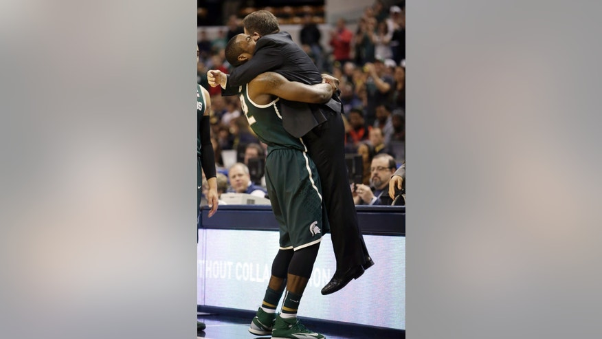 Michigan State guard/forward Branden Dawson, left, hugs head coach Tom Izzo as he walks to the bench in the second half of an NCAA college basketball game in the championship of the Big Ten Conference tournament on Sunday, March 16, 2014, in Indianapolis. Michigan State won 69-55. (AP Photo/AJ Mast)