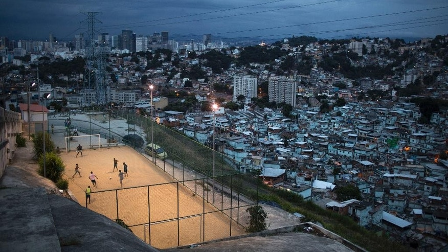 "In this March 7, 2014 photo, boys play soccer in the Sao Carlos slum after sunset in Rio de Janeiro, Brazil. The first thing Brazilian kids often do before pick-up games is play ""rock, scissors, paper"" to decide who will be goalkeeper. With so many outstanding strikers and midfielders in Brazilian history, few chose goalkeepers as their childhood idols. (AP Photo/Felipe Dana)"
