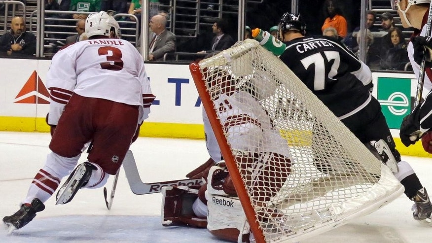 Los Angeles Kings center Jeff Carter (77) topples into the goal with Phoenix Coyotes goalie Mike Smith (41) and defenseman Keith Yandle 3) in the second period of an NHL hockey game in Los Angeles Monday, March 17, 2014.  (AP Photo/Reed Saxon)