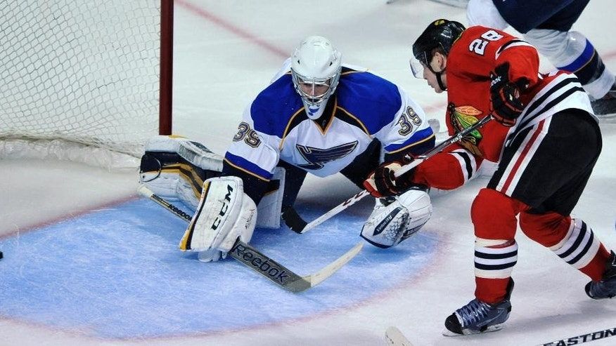 Chicago Blackhawks' Ben Smith (28), scores a goal against St. Louis Blues goalie Ryan Miller during the third period of an NHL hockey game in Chicago, Wednesday, March, 19, 2014. Chicago won 4-0. (AP Photo/Paul Beaty)