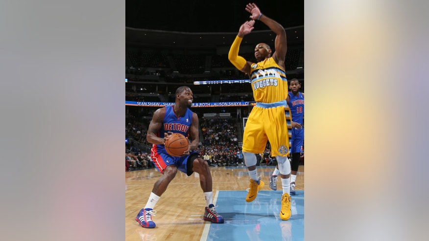 Detroit Pistons guard Rodney Stuckey, left, dodges the attempted block by Denver Nuggets guard Randy Foye in the first quarter of an NBA basketball game in Denver on Wednesday, March 19, 2014. (AP Photo/David Zalubowski)