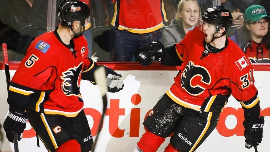Calgary Flames' Paul Byron, right, celebrates his goal with teammate Mark Giordano during third period NHL hockey action against the Buffalo Sabres in Calgary, Alberta, Tuesday, March 18, 2014. The Calgary Flames beat the Buffalo Sabres 3-1.(AP Photo/The Canadian Press, Jeff McIntosh)