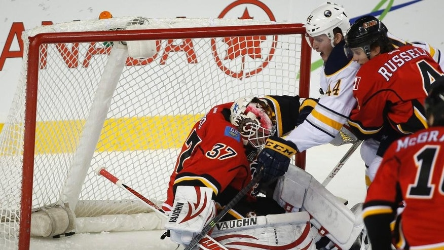 Buffalo Sabres' Nicolas Deslauriers, center, chases the puck as Calgary Flames goalie Joni Ortio, from Finland, crumples and Kris Russell, right, checks him during third period NHL hockey action in Calgary, Alberta, Tuesday, March 18, 2014. The Calgary Flames beat the Buffalo Sabres 3-1.(AP Photo/The Canadian Press, Jeff McIntosh)